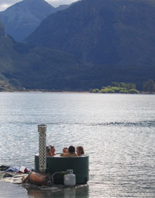 image of several people enjoying the Kiwitub at the waters edge of Pigeon Island, Lake Wakatipu